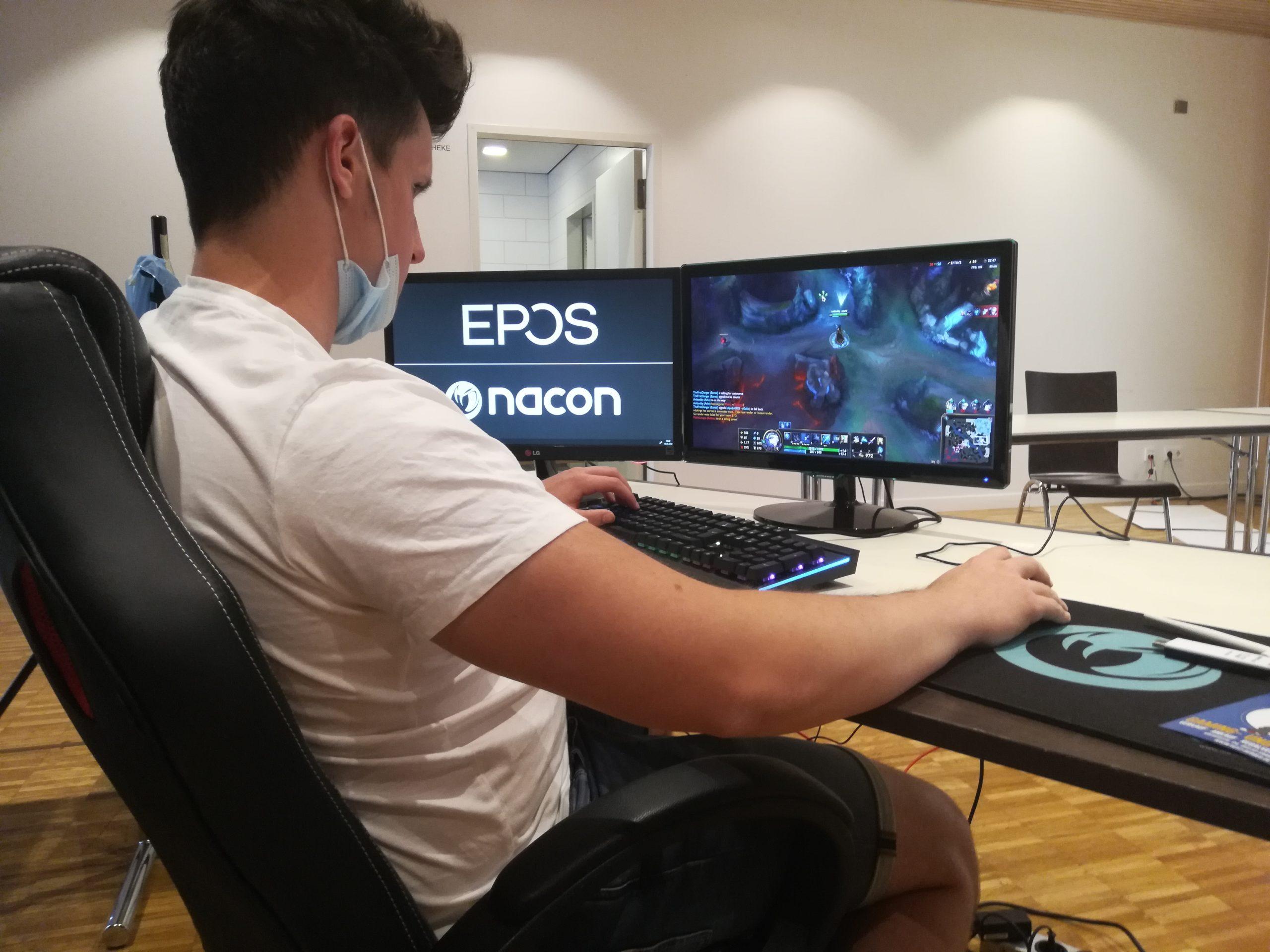 Ein junger Mann sitzt auf einem Gaming Chair und bedient die Tastatur.