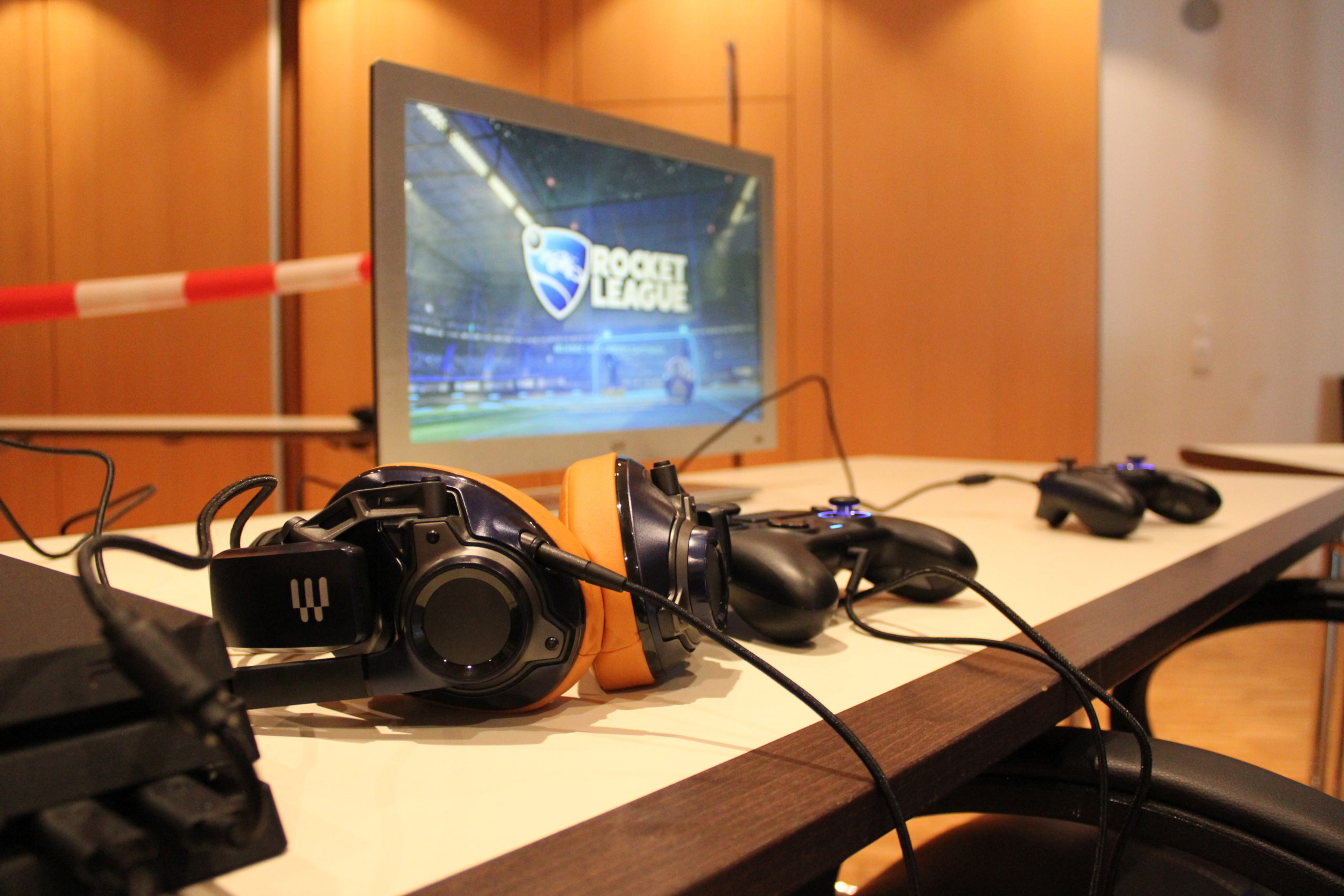 Auf einem Tisch ist ein Bildschirm, Kopfhörer und Controller aufgebaut.