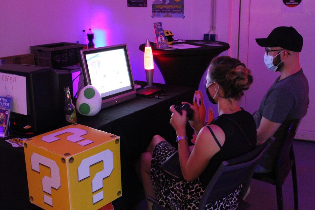 Ein Paar sitzt vor einem Bildschirm in einer Game Lounge. Zu sehen sind ein Yoshi-Ei und ein Münzblock.