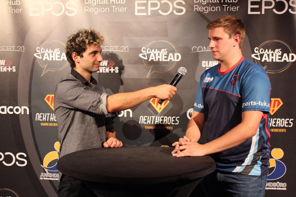 Ein Caster interviewt einen eSports-Spieler vor einer Pressewand.