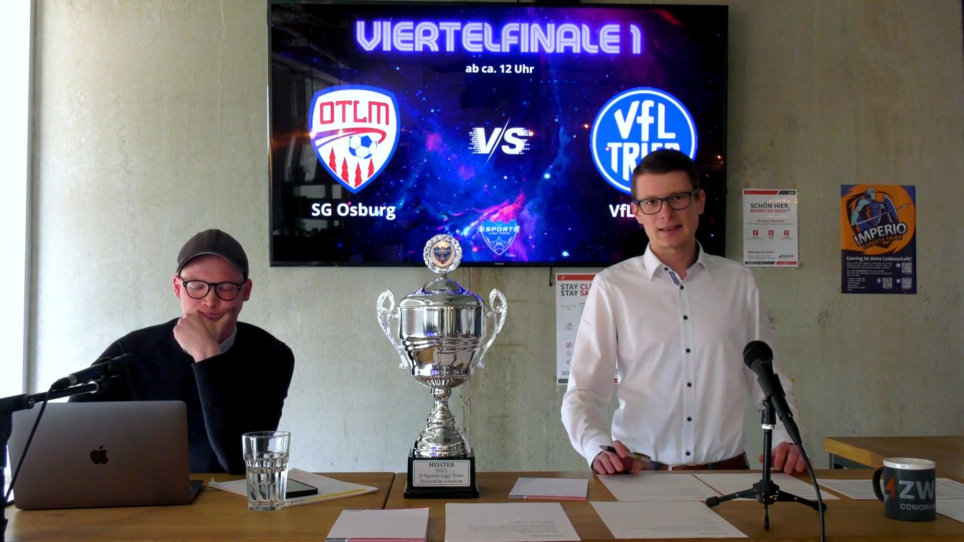 Das Studio für die eSports Liga Trier. Im Vordergrund sieht man die zwei Moderatoren und eine Live-Matchcard auf dem Fernseher dahinter.