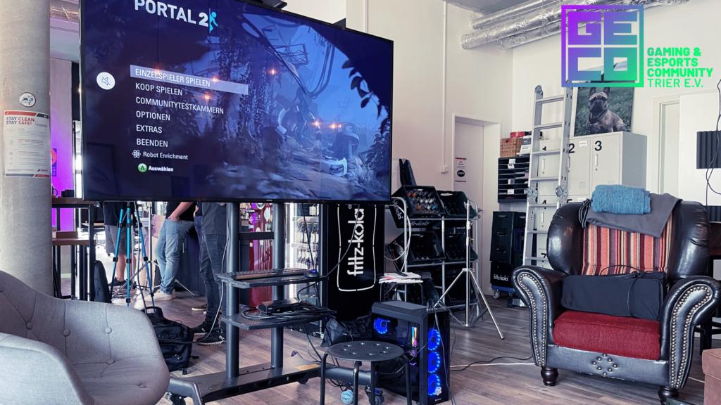 Eine Gaming-Station mit großem Fernseher im ZWO65 Coworking Space Trier. Auf dem Fernseher läuft das Spiel Portal 2.