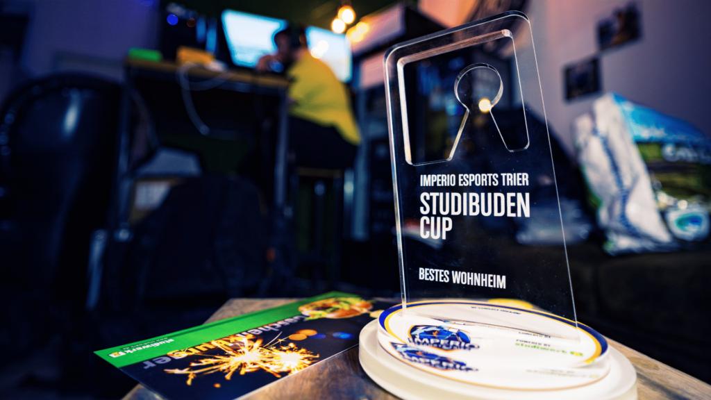 Der Pokal des Studibudencups. Er ist durchsichtig und enthält das Logo des Studiwerks Trier sowie den Schriftzug des Turnieres.